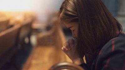 Mulher rezando a igreja