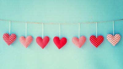 Varal com vários corações estofados pendurados. Cada um possui uma estampa diferente, mas todos em tons de vermelho e rosa.