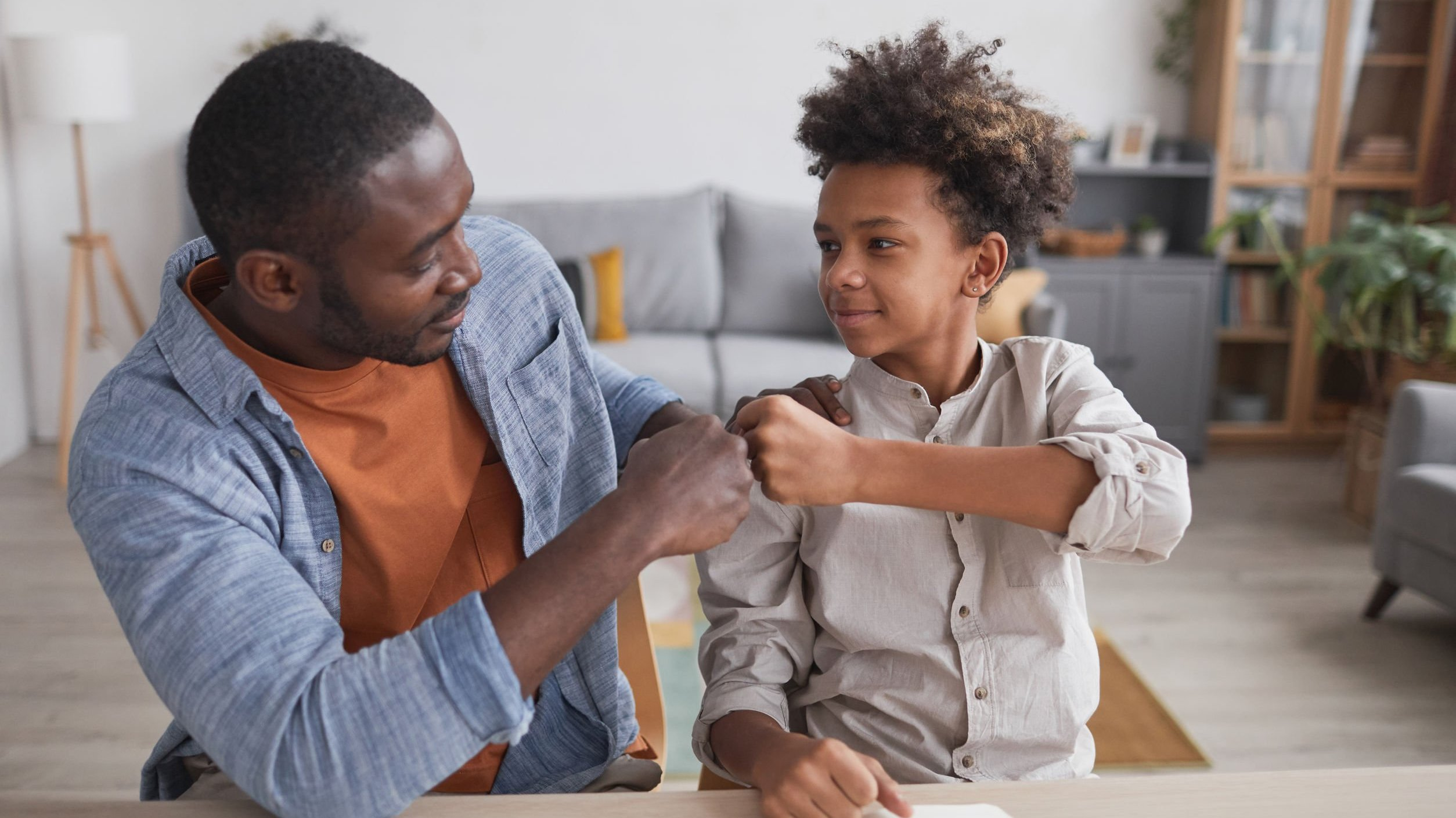 Pai e filho unem as mãos em gesto simbólico.