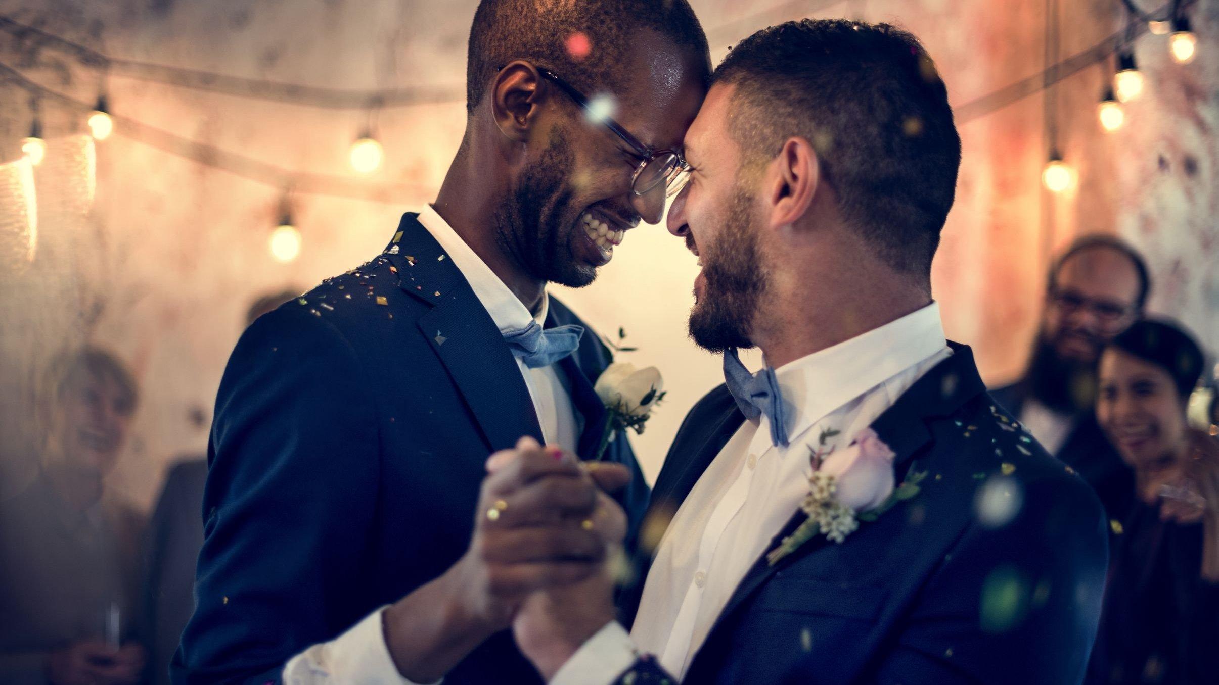 Casal dançando e sorrindo vestidos com roupas de casamento