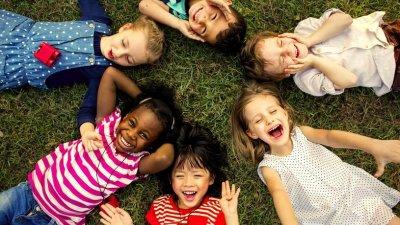 Crianças deitadas na grama, em círculo, sorrindo