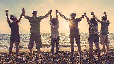 Grupo de amigos vendo o pôr do sol e dando as mãos na praia