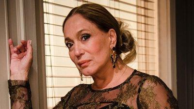 Susana Vieira com vestido preto e cabelo preso em coque, encosta em cortina.