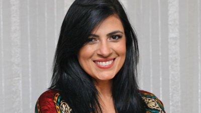 Fernanda Brum sorrindo com cabelos soltos e blusa estampada
