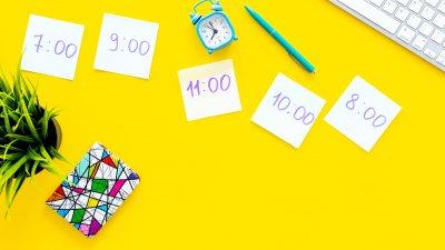 Mesa comum relógio e várias notas de papel com horários do dia escritos.