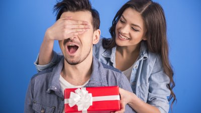Mulher dando um presente surpresa para homem.
