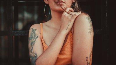 Mulher se abraçando com tatuagens nos braços