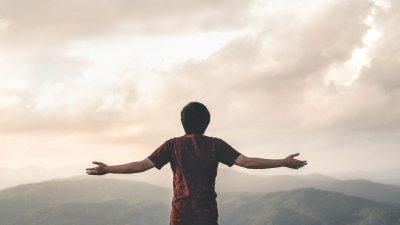 Homem visto de costas com os braços abertos sobre paisagem natural.