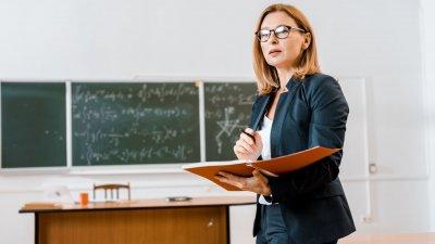 Professora ensinando garoto a fazer cálculo na lousa.