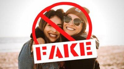 Duas mulheres abraçadas com a palavra 'FAKE' escrita embaixo