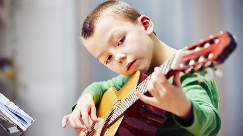 Criança tocando violão