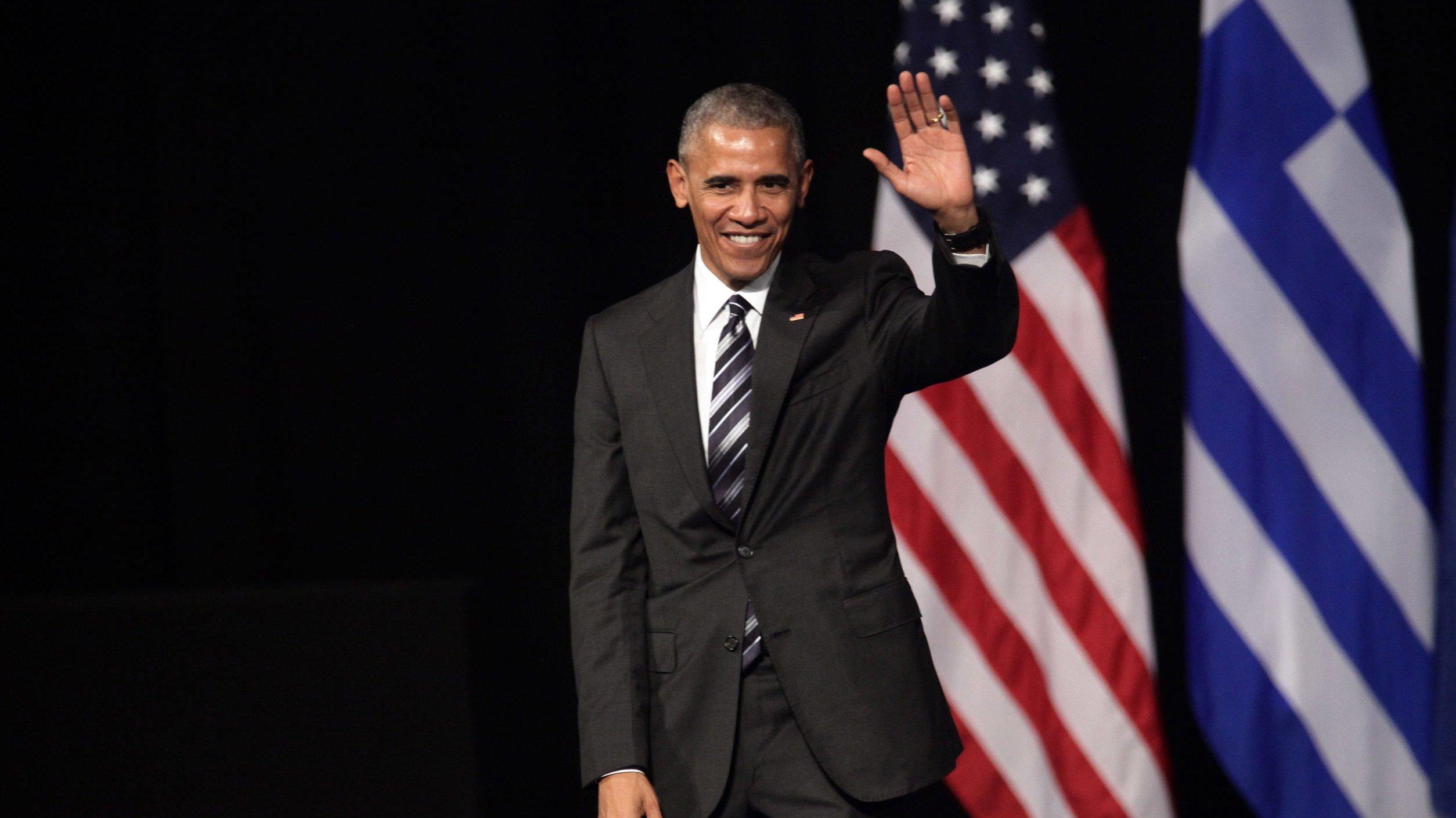 Barack Obama acenando ao lado da bandeira dos Estados Unidos