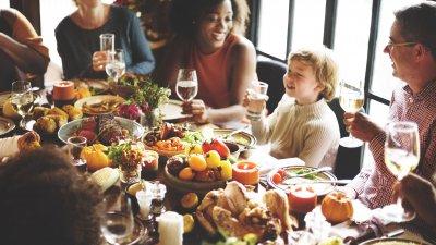 Família sentada ao redor de uma mesa durante jantar de Dia de Ação de Graças.