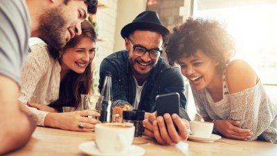 Amigos em mesa dando risada olhando para celular