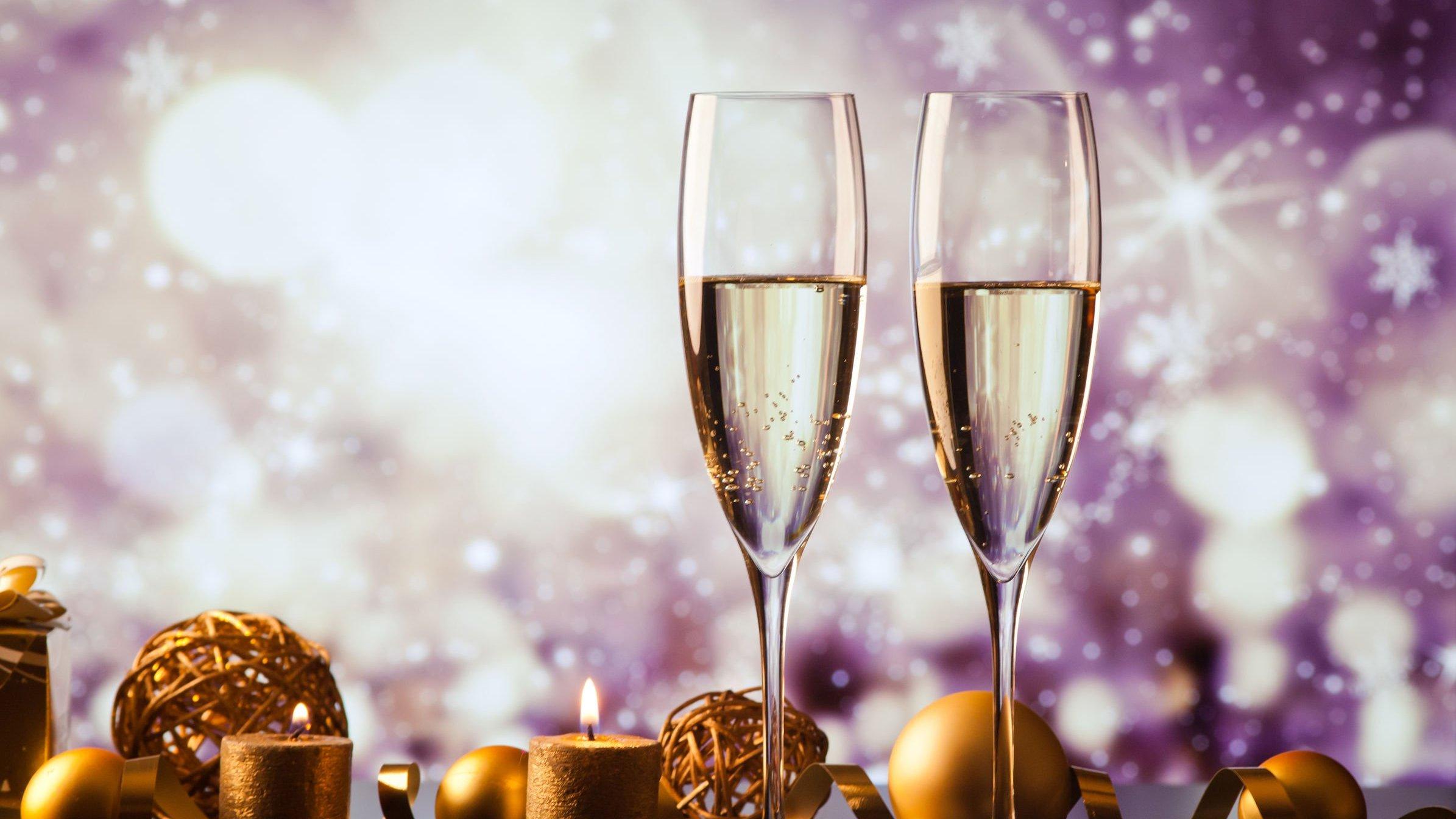 Taças de champanhe ao lado de adereços natalinos.