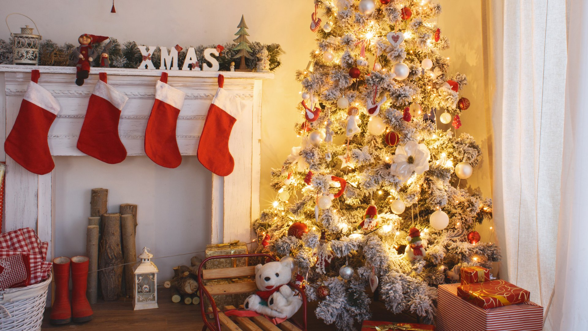 Árvore de natal iluminada com presentes de natal embaixo e meias penduradas na lareira
