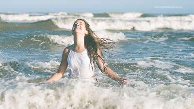Mulher sorrindo entre as ondas do mar.