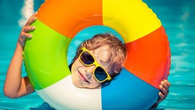 Criança com uma boia colorida em volta da cabeça e usando óculos de sol amarelo