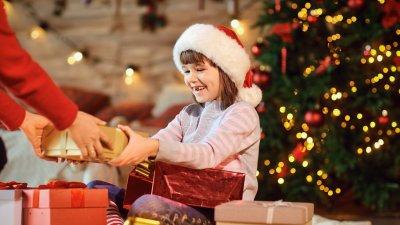 Garota colocando enfeite de natal na árvore