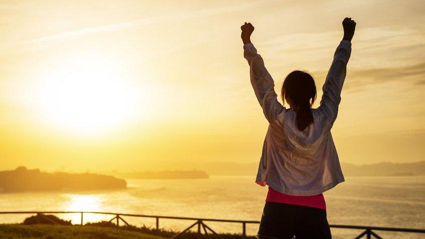 Garota com os braços erguidos admirando o pôr do sol