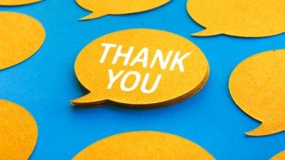 Pessoa escrevendo Thank You (obrigado, em inglês) em post-it