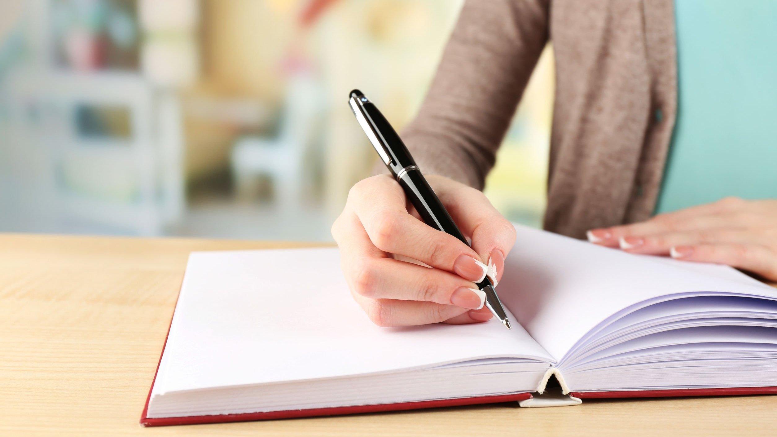 Mulher escrevendo em um caderno em branco