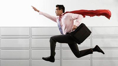 Homem com capa de super-herói e maleta executiva dando salto