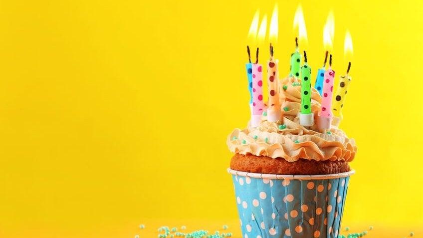 Cupcake colorido com várias velinhas de aniversário acesas em um fundo amarelo