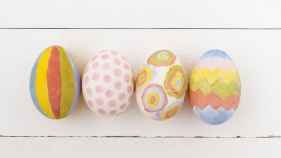 Ovos coloridos e estampados numa mesa de madeira branca.