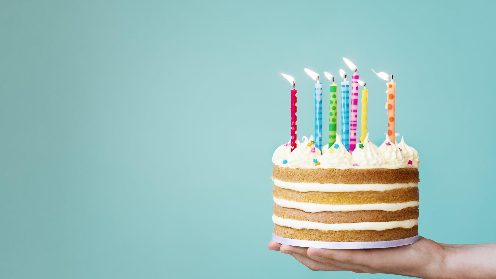 Pessoa segurando bolo de aniversário com velas acesas