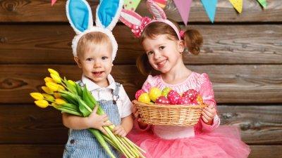 Menina e menino pequenos com orelhas de coelho. O menino segura um buquê de flores, enquanto a menina segura uma pequena cesta cheia de ovos coloridos.