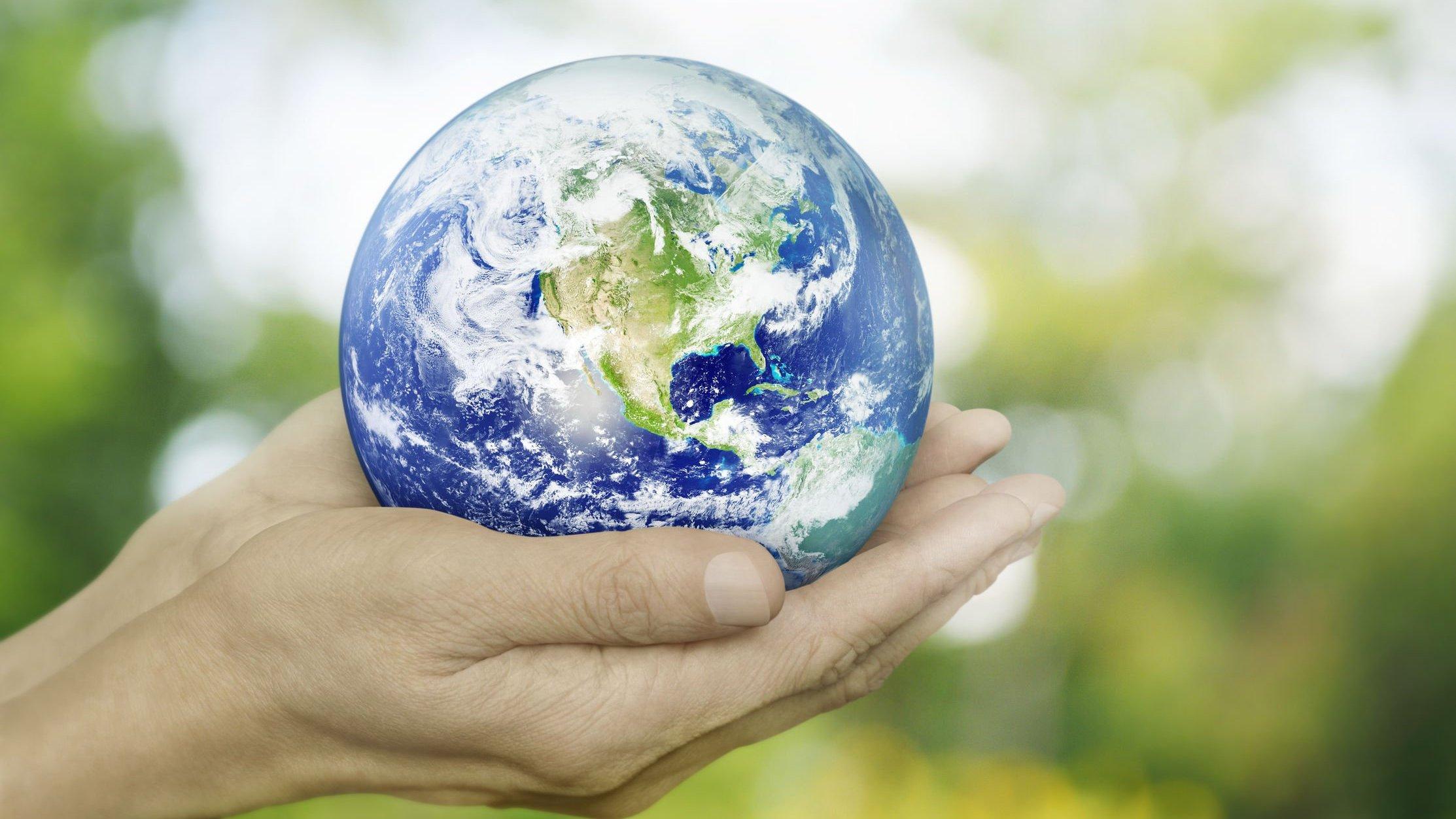 Mãos segurando uma miniatura do planeta Terra.