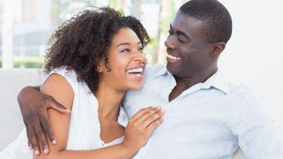 Homem e mulher abraçados, sorrindo um para o outro.