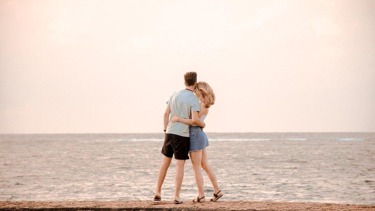 Homem e mulher abraçados de frente para o mar.