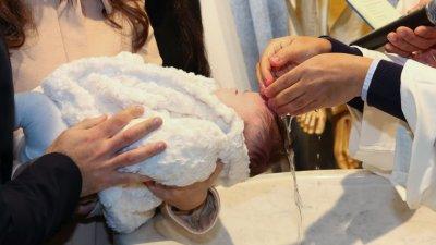 Bebê no colo da mãe, recebe água benta das mãos de um padre em sua cabeça.