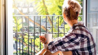 Mulher abrindo a janela de manhã enquanto segura uma caneca