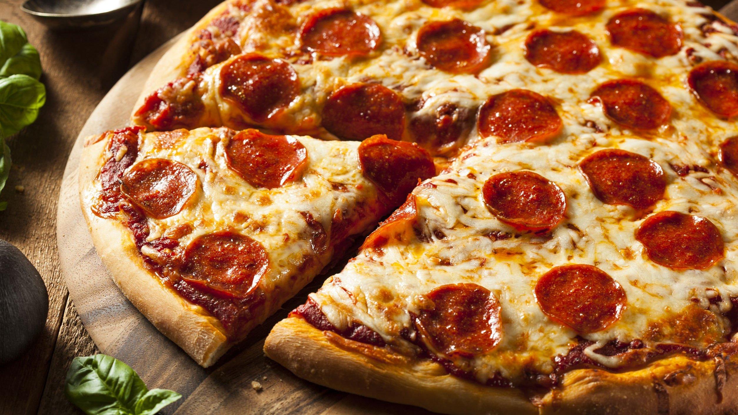 Pizza de pepperoni e queijo em uma mesa