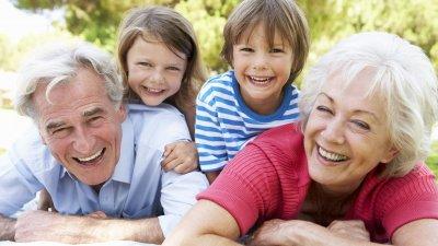 Um homem e uma mulher, ambos idosos, deitados de bruços na grama e rindo. Nas costas deles, estão deitados um menino e uma menina, que também estão rindo.