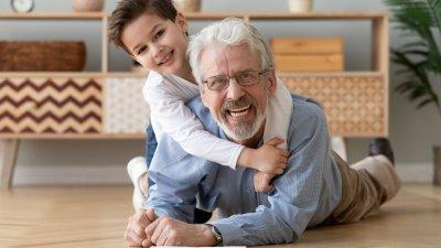 Avô e neto brancos sorrindo deitados no chão de uma sala.