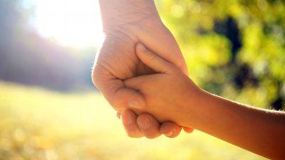 Pai segura a mão de uma criança pequena.