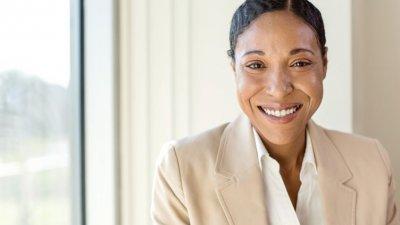 Mulher com roupa social e cabelo preso sorrindo
