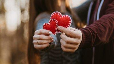 Casal segurando letras que formam a palavra Love (amor em inglês)