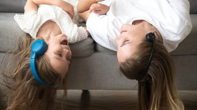 Amigas ouvindo música com fones de ouvido deitadas no sofá de cabeça para baixo