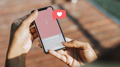 Pessoa segurando um celular com um coração saindo de um balão de fala.