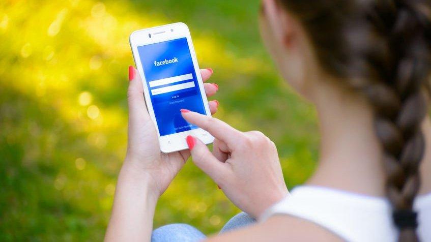 Mulher usando o aplicativo do Facebook em seu celular