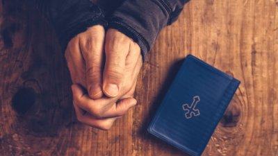 Mãos unidas com bíblia pequena ao lado vista de cima