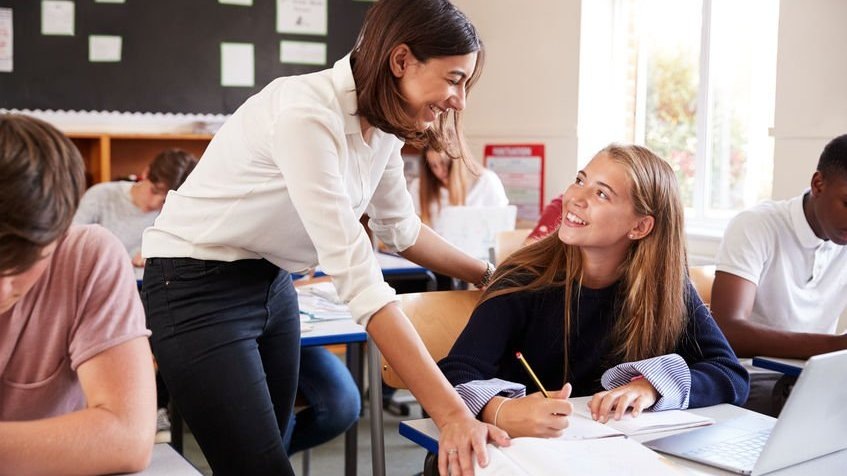 Professora sorrindo para aluna
