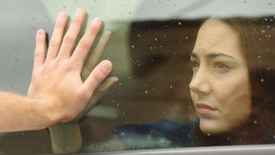 Mulher dentro de carro encostando a mão no vidro e pessoa encostando-o do lado de fora