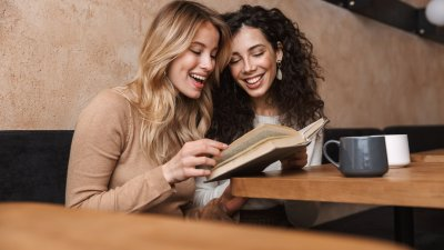 Amigas lendo um livro e sorrindo em frente a uma mesa