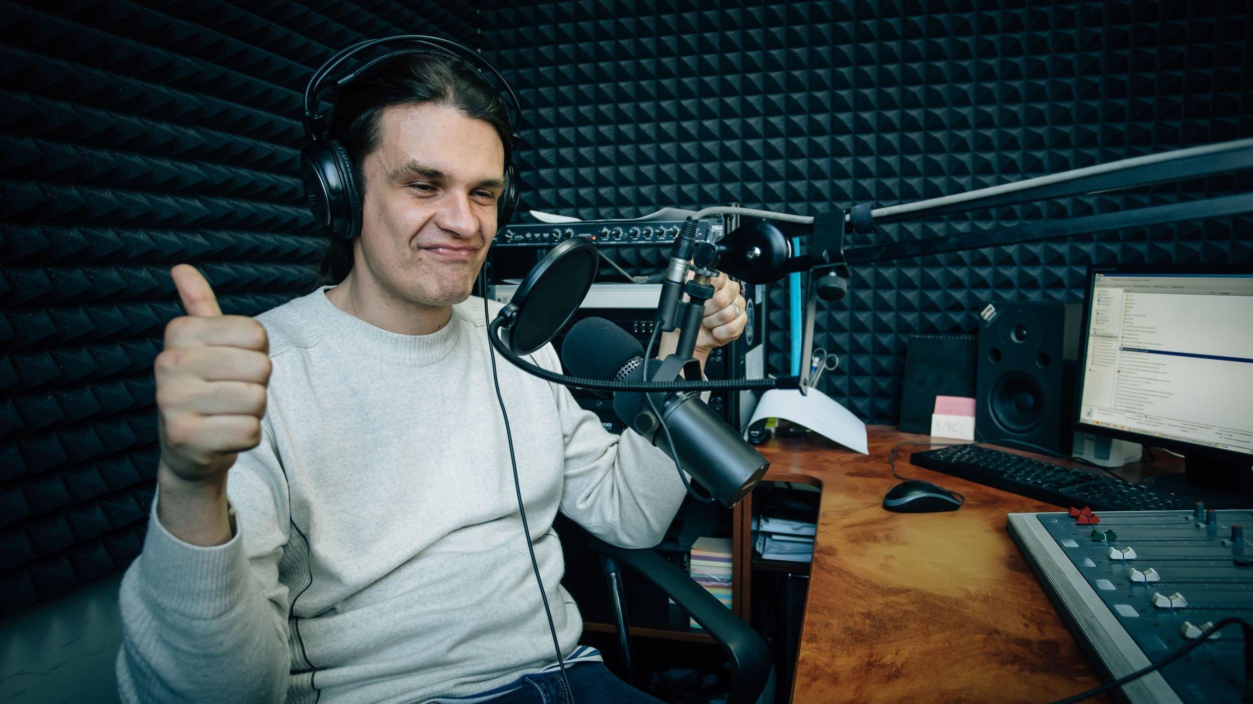 Homem branco com polegar levantado, usando fones de ouvidos e elementos eletrônicos.